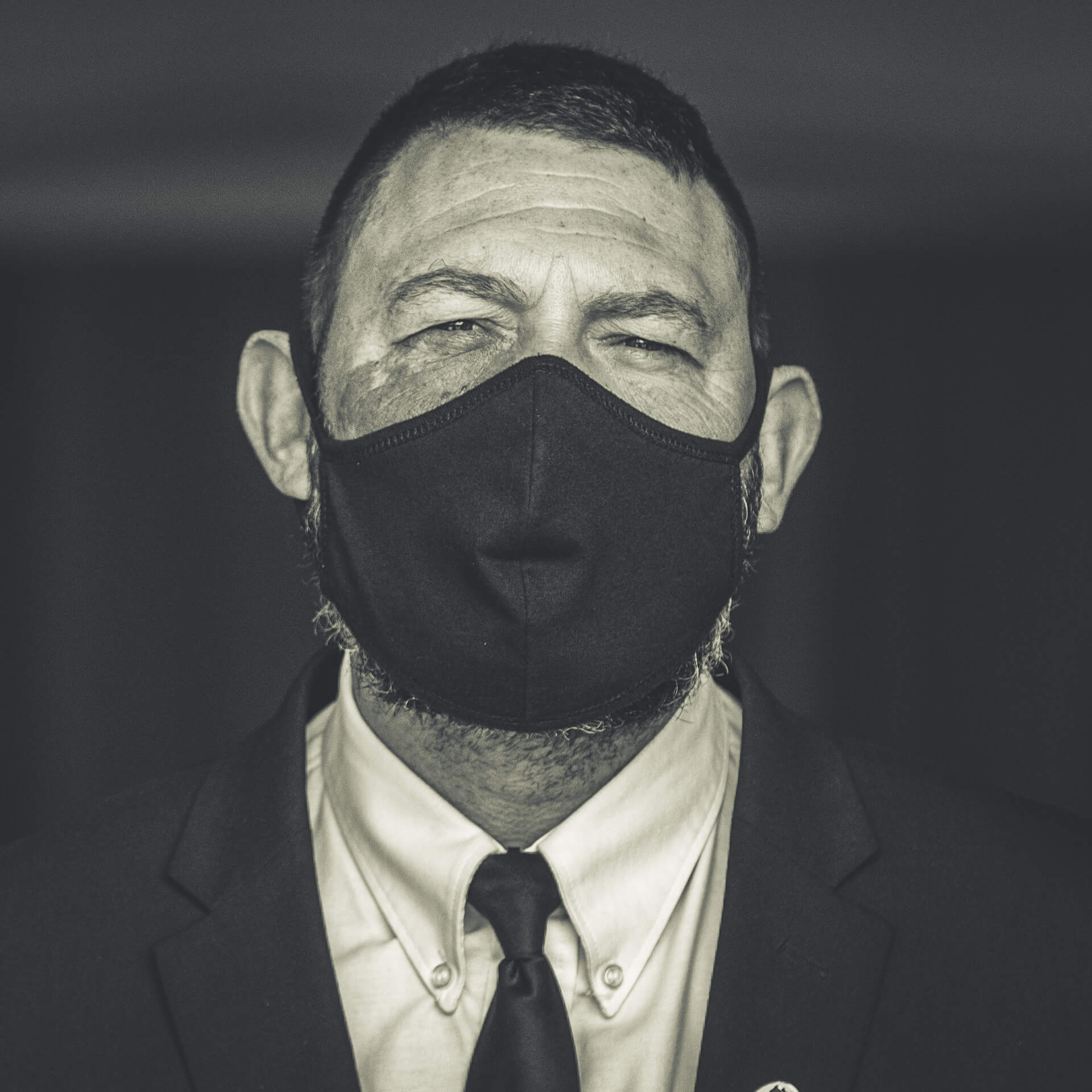 Adam, a Chapel Attendant at the Vale Cremaorium, Fladbury, (seen in Black & White) stands at the Chapel door awaiting mourners. He is wearing a black coloured Face Mask.