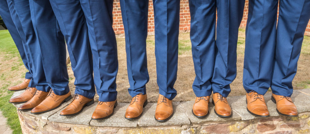 The 6 Best Men show off their matching light brown shoes whilst stood on a low curved wall