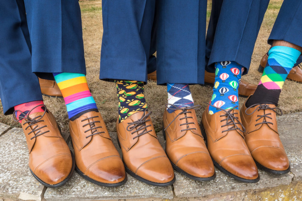 The Best Men show of their uniform shoes. All are wearing unique colourful socks