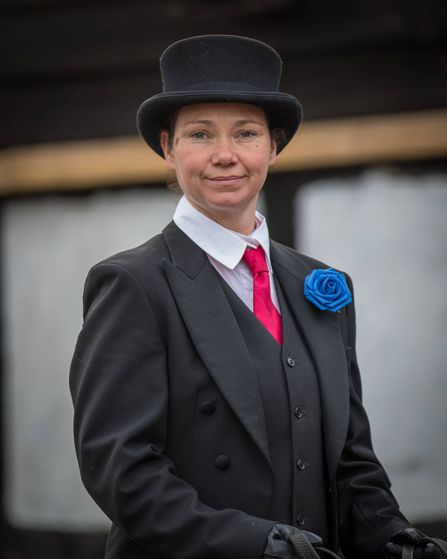 Lucy Smith of The Blackthorne Carriage Company. The Blackthorne Carriage Company is a provider of Horse Drawn Carriages for Funerals, Weddings etc. They are Worcestershire based but travel country wide. Lucy is one of their professional out riders. She is seen here, looking straight at the camera, in a colour waist up shot as she prepares for a funeral. She wears traditional attire along with a red tie, and a blue button hole flower.