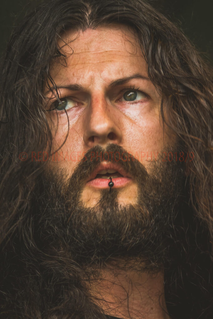 A close up head shot of a long haired/bearded guitarist at The Drunken Monkey Rock Festival 2019. He has his bottom lip pierced and wears a black ring in it.