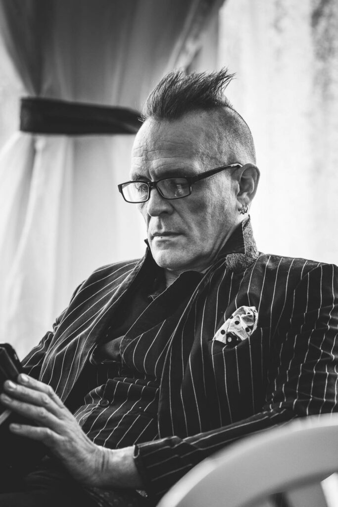 A B&W image of Mr John Robb of The Membranes sat backstage reading (on his digital device) whilst at Lakefest 2019.