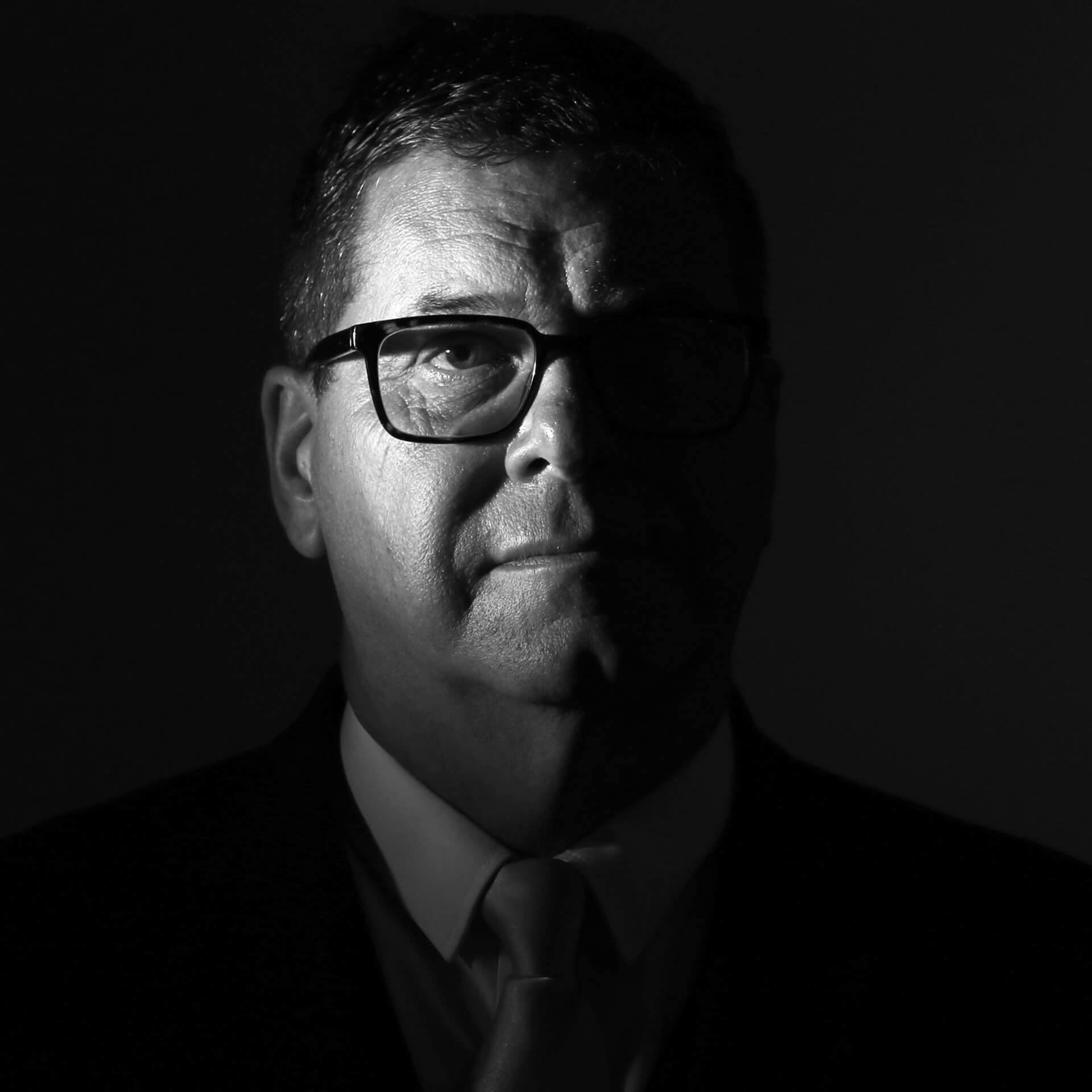 An 'eerie' style B&W image of Tim Hodges. Tim is the Welfare guy at a local Funeral Directors. The images shows Tim's head and neck, with it being side lit to emphasise only the RHS of his head .