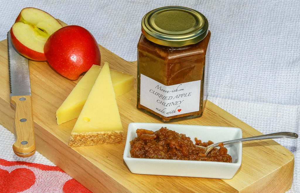 A Jar of Mooreish Curried Apple Chutney Accompanied By Two Chunks of Cheese and A Sliced Fresh Apple On A Serving Board