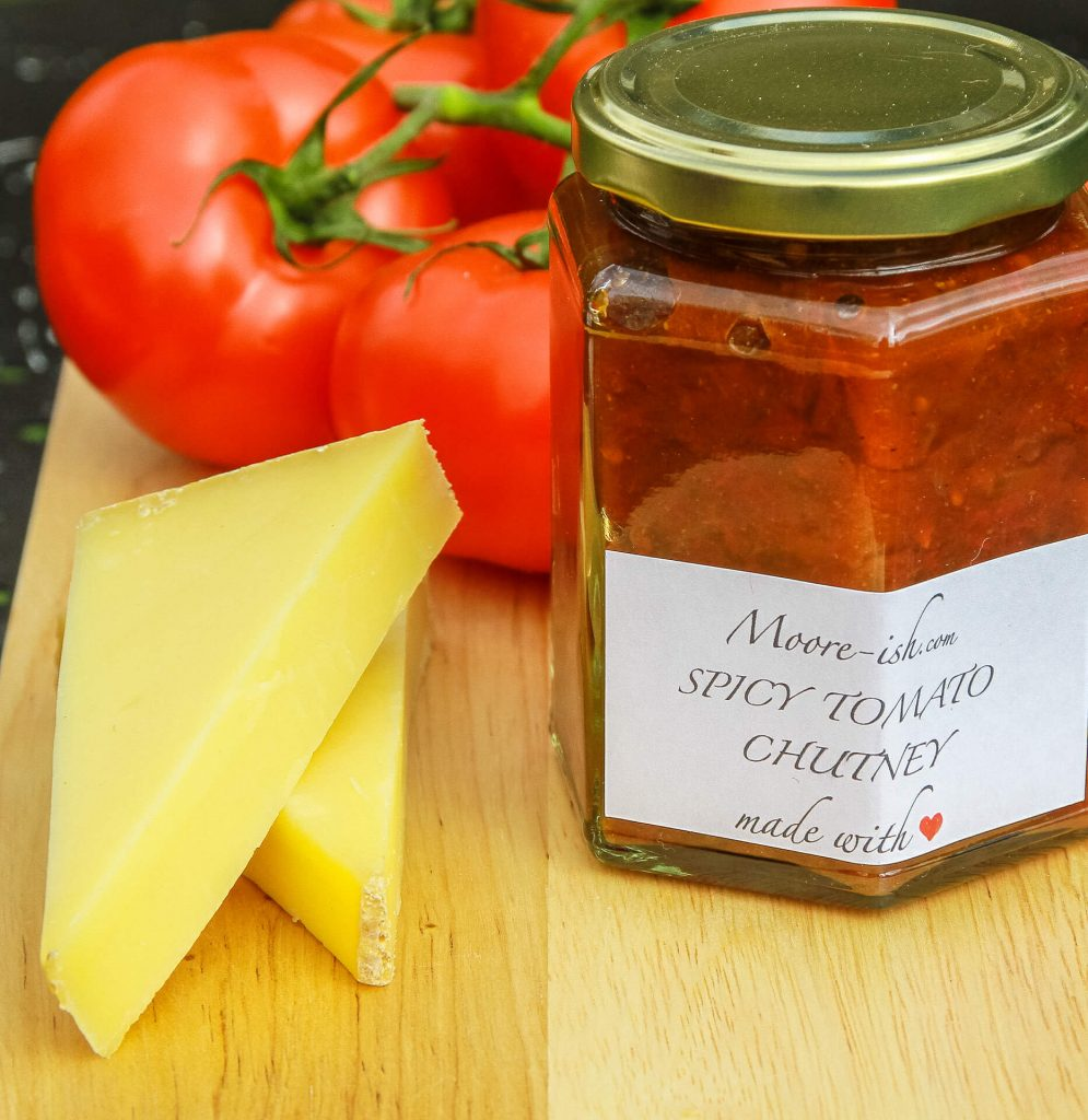 A Jar of Mooreish Spicy Tomato Chutney Accompanied By Two Chunks of Cheese and Fresh Vine Tomatoes