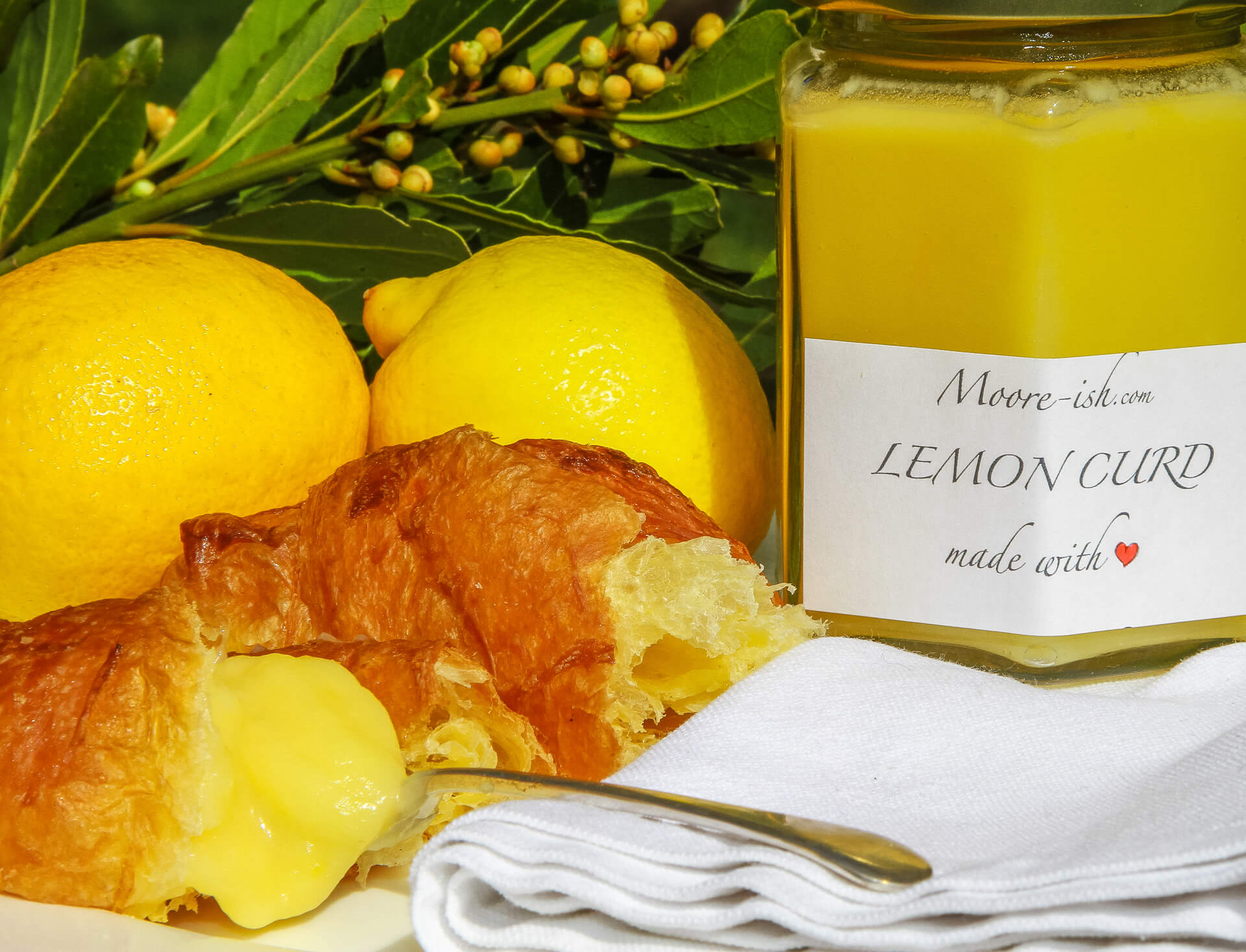 A Fresh Croissant With A Generous Helping of Lemon Curd On A Spoon and A Jar Of Mooreish Lemon Curd