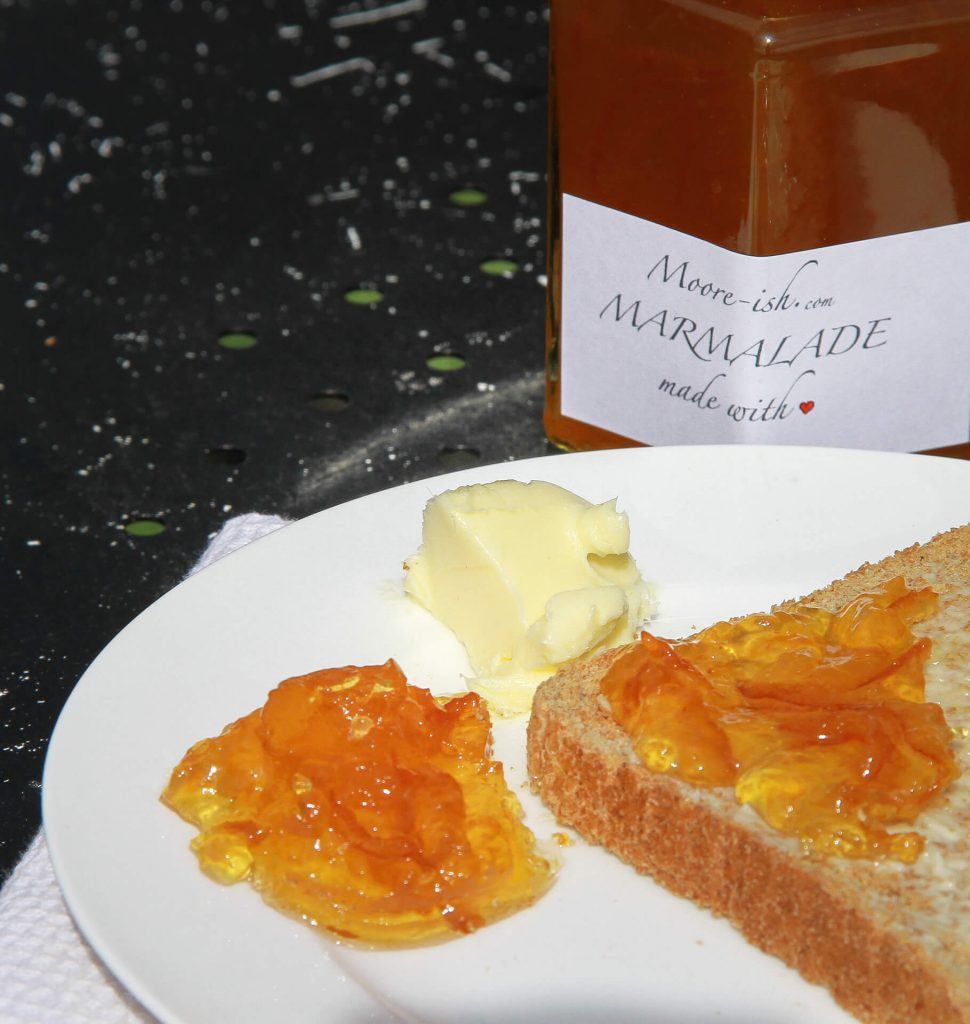 A Jar Of Mooreish Marmalade Behind A Slice Of Toast & Marmalade On A Plain White Plate With A Dollop Of Marmalade & A Knob Of Butter On The Side