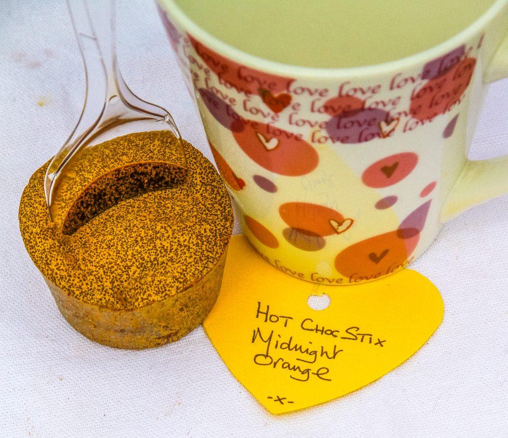 Hot Choc Stix Chocolate Midnight Orange Flavoured Mix On A Spoon Next To A Mug