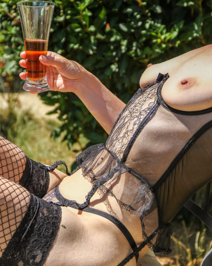 A thigh to chest only colour image of Liz, sat in the garden with a half full glass of Pimms in her right hand. Liz is bare breasted, and she wears a see through lacey bodice, black hold up fishnet stockings, and a black thong.