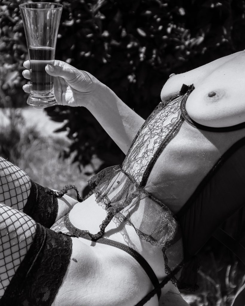 A black & white thigh to chest only image of Liz, sat in the garden with a half full glass of Pimms in her right hand. Liz is bare breasted, and she wears a see through lacey bodice, black hold up fishnet stockings, and a black thong.