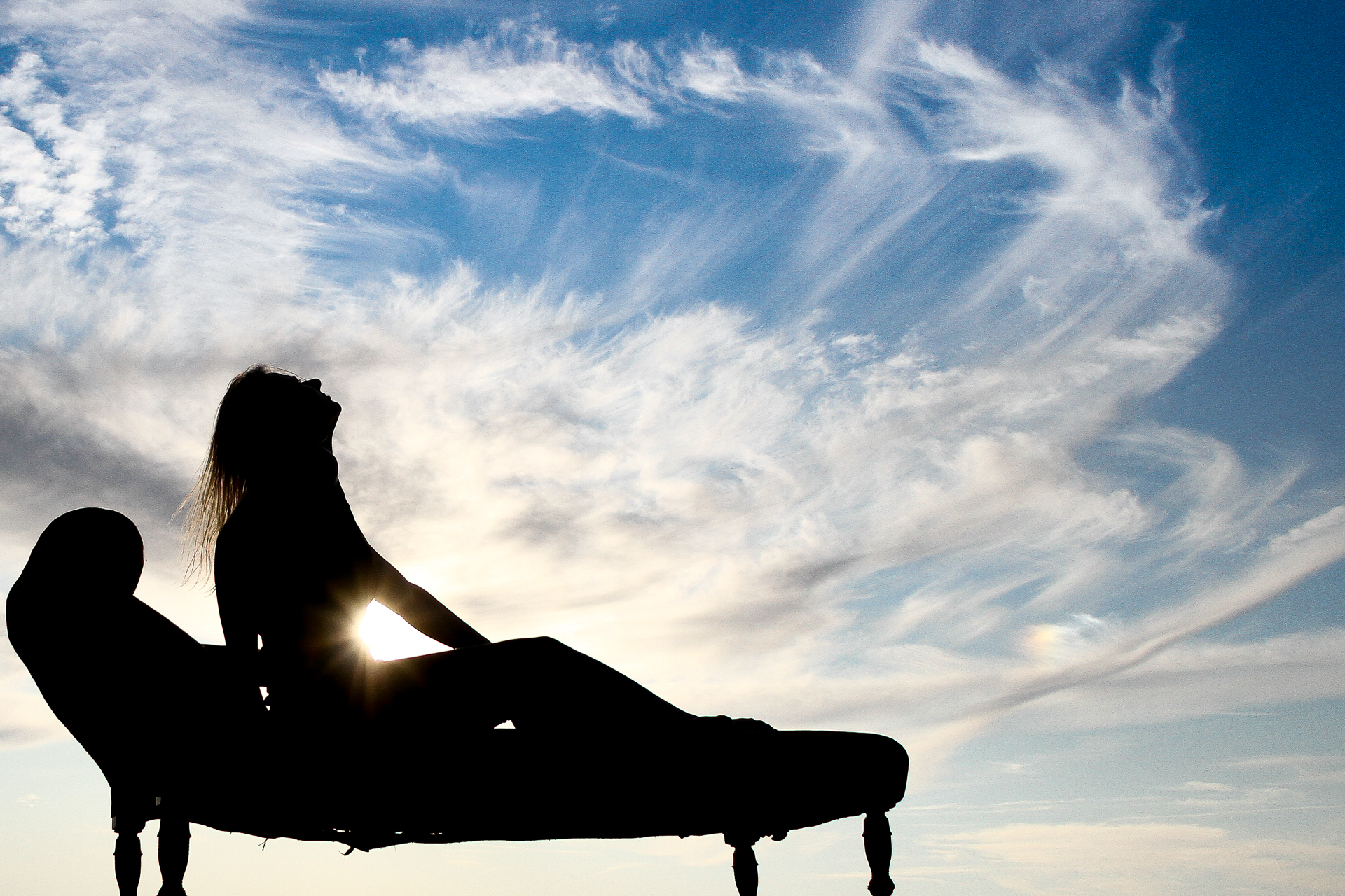 Set against a vivid blue sky populated with cirrus clouds Liz who is seen in silhouette sat on a Chaise Lounge. The sun can be seen poking out just between her stomach and her outstretched arm.
