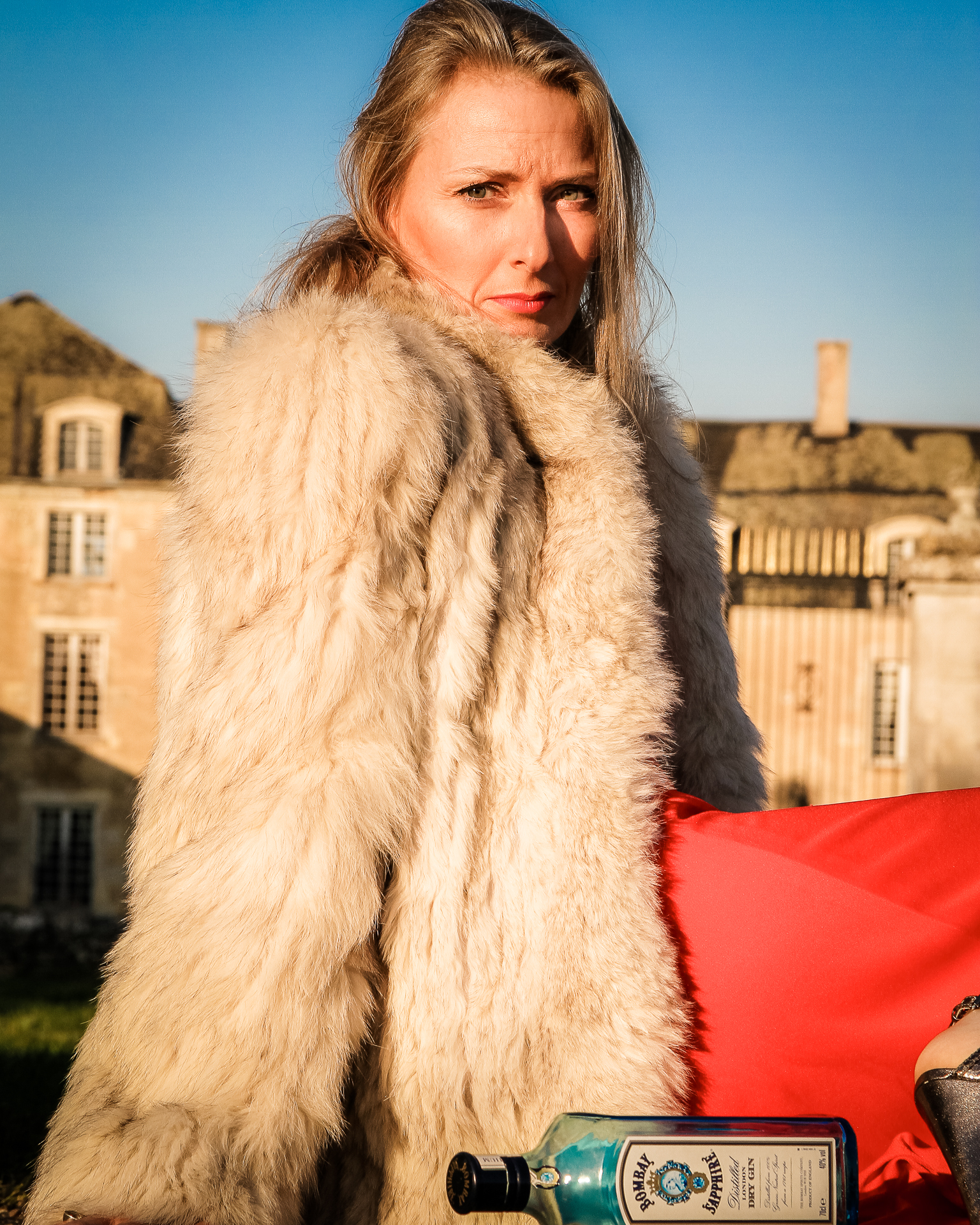 Liz is seen in a red evening gown with a fake fur coat, and black heels sat on the floor in front of a French Chateau, at dawn, with an empty Bombay Sapphire bottle laying in front of her. Her long blonde hair is unkempt, suggesting it was an 'eventful' night.