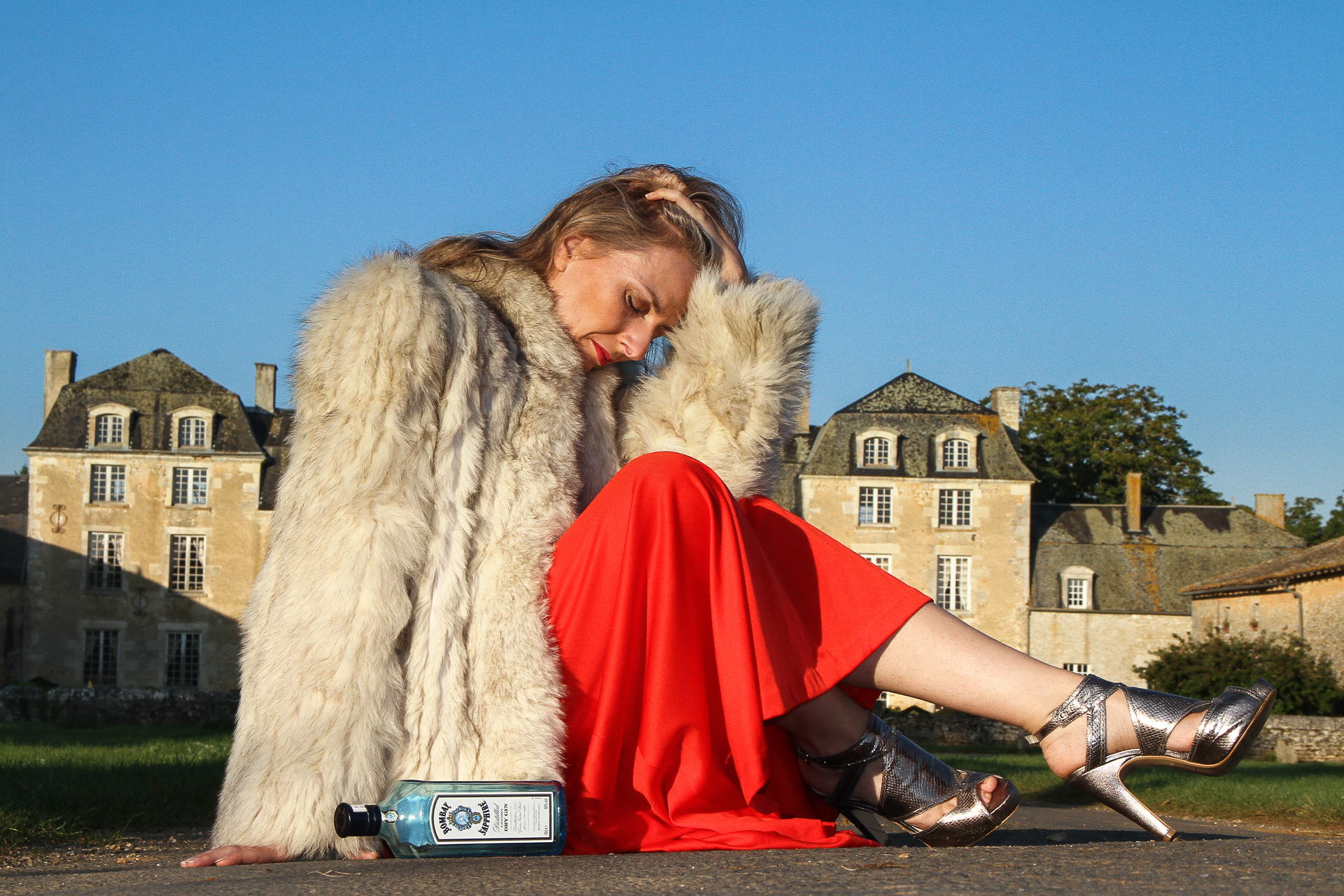 Liz is seen in a red evening gown wearing a fake fur coat, and silver heels, sat on the floor in front of a French Chateau. She has both legs tucked up towards her body, her left hand is on her bowed head, and her fingers are in her hair.  By her side there is an empty Bombay Sapphire bottle. Her long blonde hair is messy, suggesting it was an eventful night.