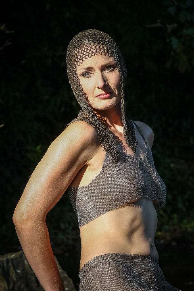 Seen here in a waist up colour image is Liz. Set against a black background, a tanned Liz wears a chain mail headdress, a chainmail seethrough bra, and chainmail shorts. Liz is turned half to her left hand side, with her hands behind her back, but she has her head turned to her right hand side and she looks directly into the camera.