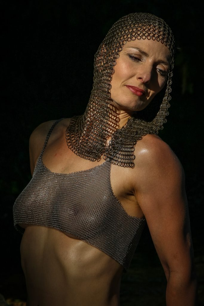 Seen in a waist up colour image is Liz. Set against a black background, a tanned Liz wears a chain mail headress and a chainmail seethrough bra. Liz is turned half to her right side, but she looks down and to her left hand side.