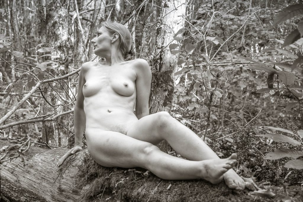 A full length body black & white shot of liz as she sits on an old moss covered fallen tree in a wood, she is completely naked. Her body faces the camera whilst she turns her head and looks away to her right hand side. She has her right arm behind her, to steady herself and her left arm is by her side. She has her left leg slightly bent with her right leg out straight with her foot pointed upwards,  Taken in France in 2011.