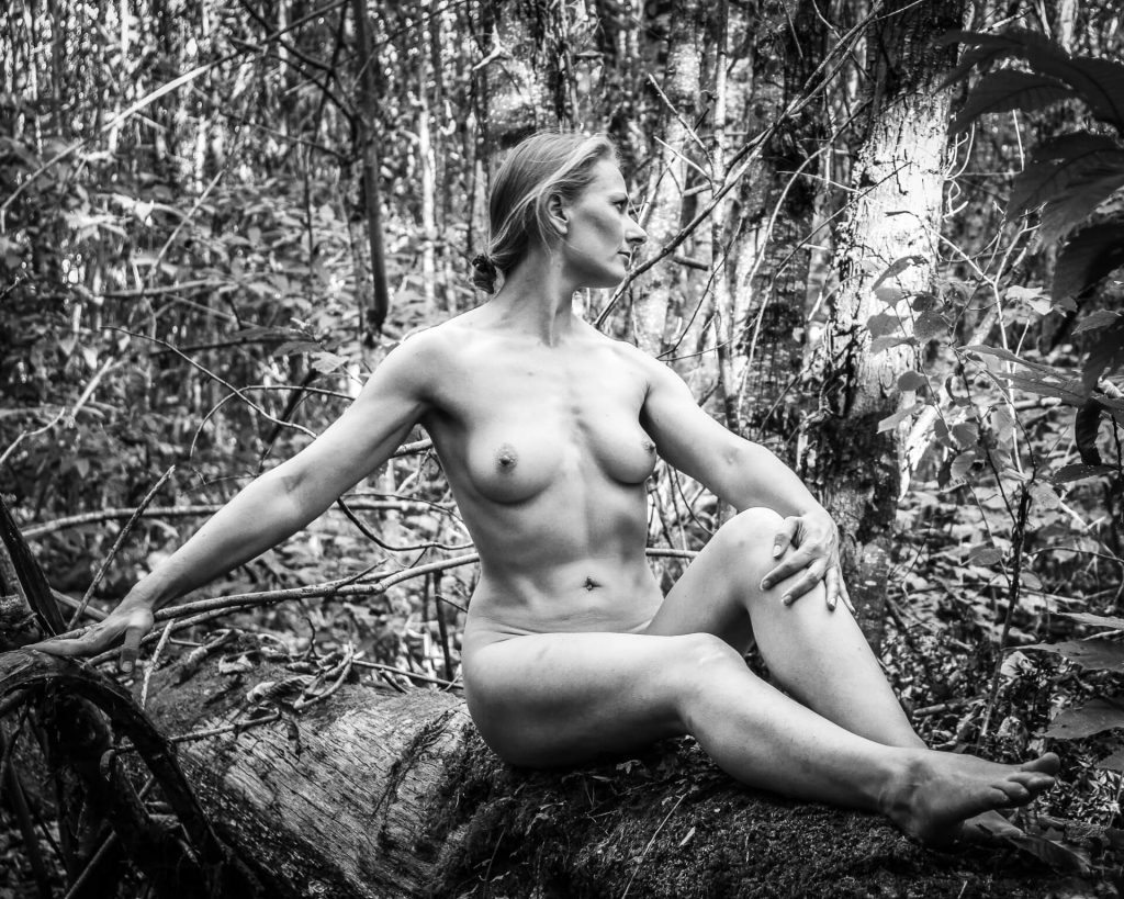 A full body length black & white image of Liz. Liz sits on an old moss covered fallen tree in a French wood, she is completely naked. Her body is turned towards the camera (displaying her very well proportioned chest) whilst she turns her head and looks away to her left hand side. She has her right arm out to her RHS resting on a branch her in order to steady herself. Her left leg is bent slightly upwards towards her chest, and her left arm is holding her knee. She wears her hair pulled back and in a 'scrunchie'.
