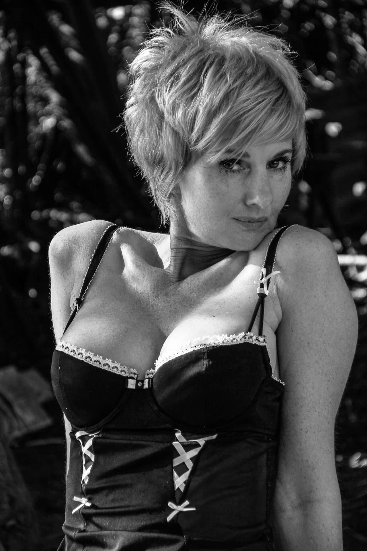 A black & white image of Rebbeca. She wears a black corset (with white edging) which shows off her ample chest. In this waist up image her body half faces the camera with her head (sporting a relatively short spiky hair cut) turned to her left. Her eyes though look provocatively directly at the camera.