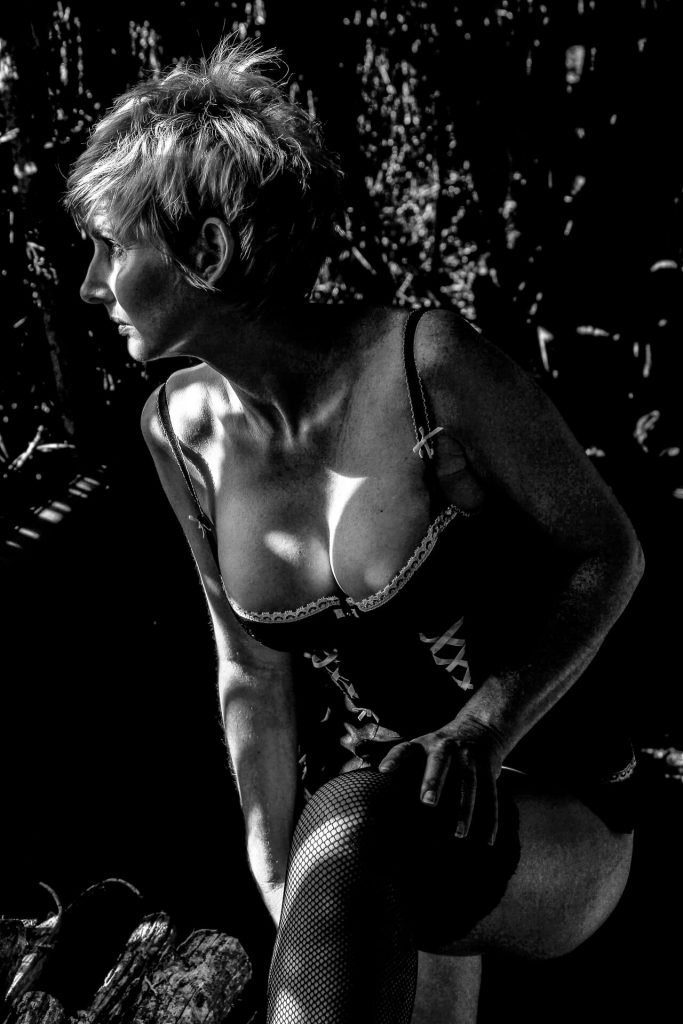 A 3/4 length black & white image of a blonde short spike haired Rebbeca. Rebbeca is seen in a wood. shed with beams of sun light highlighting areas on her body. She is seen posing in a lacy black coloured corset style bodice, which just about contains her 'more than ample assets', along with black fishnet stockings. Rebbeca is stood leaning slightly forwards with her left leg bent and her left foot (out of shot) on a chopping block. She looks out to her right, and she has both hands resting on her left thigh.