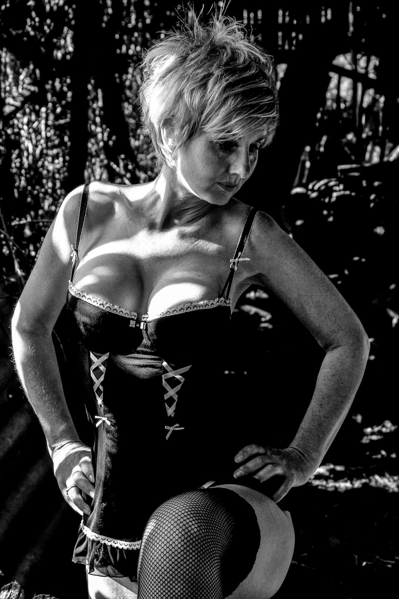 A 3/4 length black & white image of a blonde short haired Rebbeca. Rebbeca is seen posing in a lacy black coloured corset style bodice, which just about contains her 'more than ample assets', she also wears black fishnet stockings. Rebbeca is stood with her left leg bent and her left foot (out of shot) on a stool. She looks down and to her left, and she has both hands on her hips.