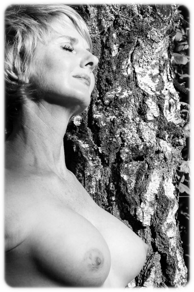 A head & chest black & white post cardesque image of Rebbeca. She is topless and this image shows off her more than ample chest exceptionally well. In this image, taken from her 1/2 right and slightly below her chest position, she is seen leaning against a tree trunk. She has her eyes closed and has a look of a relaxed manner as her face points in the same direction as her body. She sports a relatively short spiky hair cut.