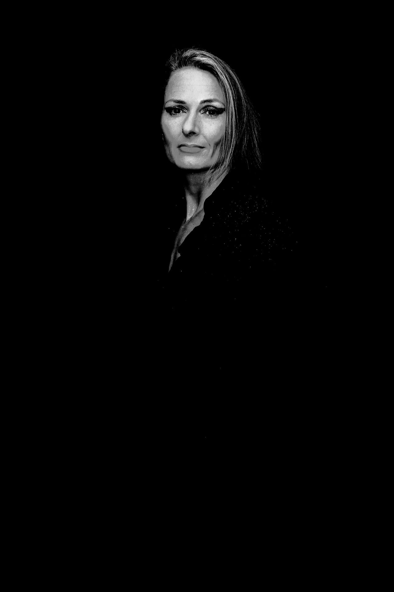 A 3/4 length body shot in black & white of Liz. Her body is facing to the left of the camera, although she has her head turned towards and is facing the camera, she looks directly at the lens. Only her head is lit and is therefore visible in the image, the remainder of the image and background are black. She has her hair over the left of her head, and a serious expression upon her face.