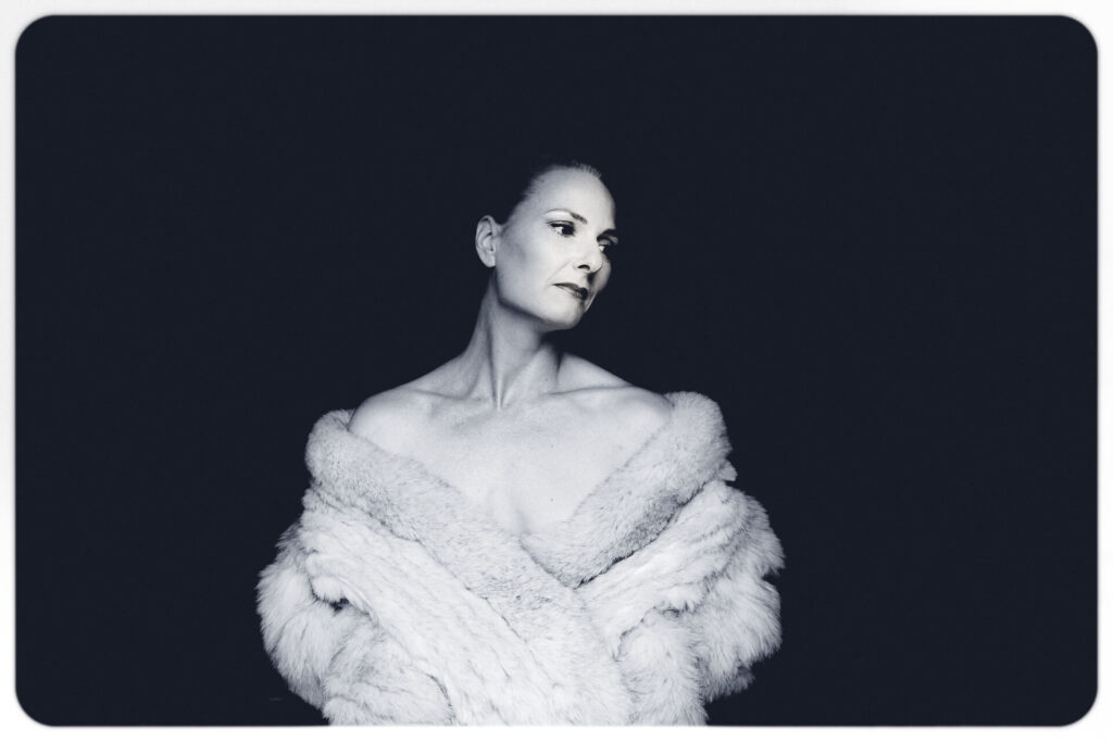 A B&W waist up image of Liz only wearing an off the shoulders imitation fur jacket, and not much else, taken in a cave in France in 2011.