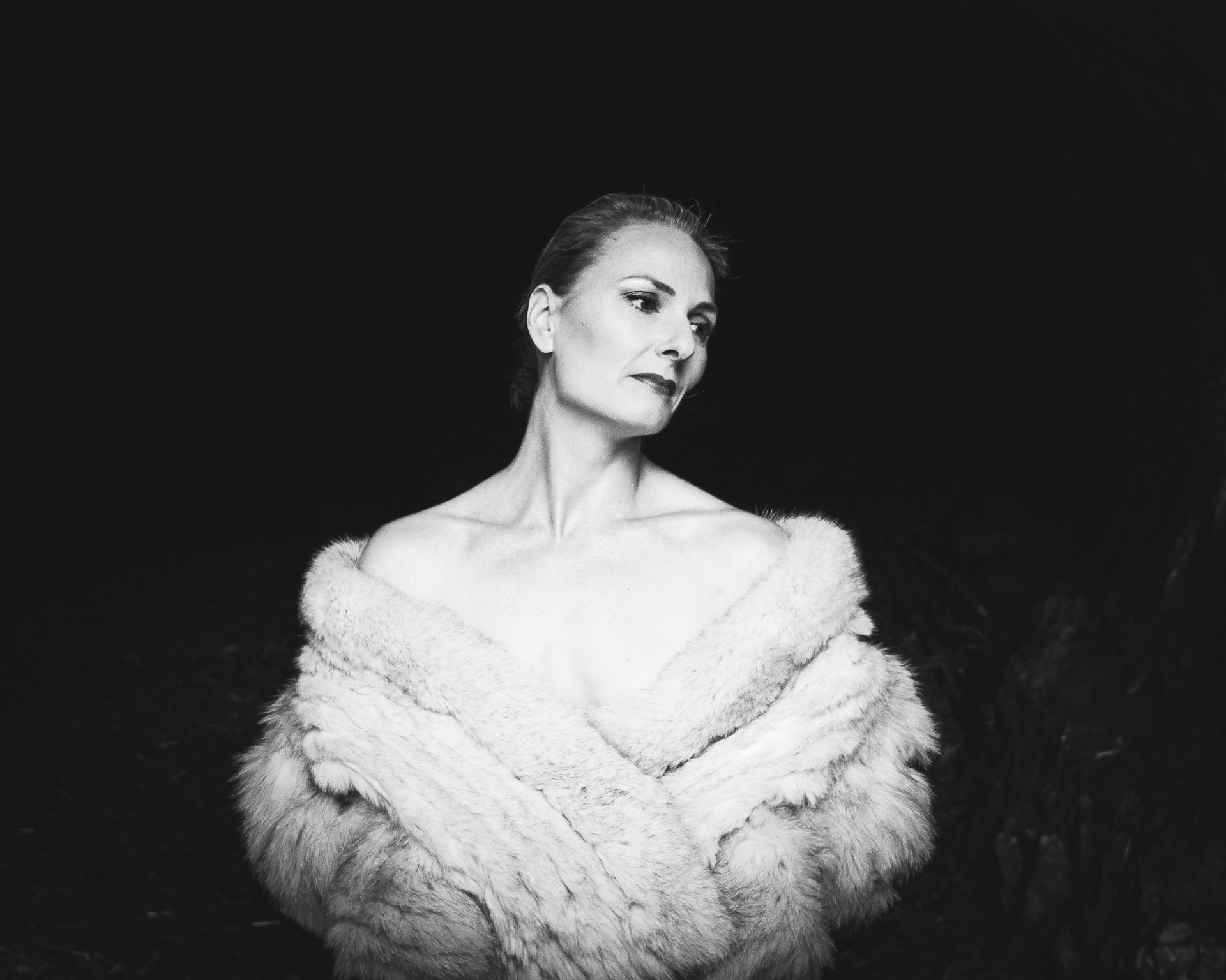 A black & white image of Liz from the waist upwards, against a black background. Liz is naked, save a fake fur coat that is worn off her shoulders, she holds it together at her waist allowing just a hint of 'tease'. Liz wears her hair pulled hard back, this is complimented by very effective harsh make-up, giving an old fashioned classic appearance.