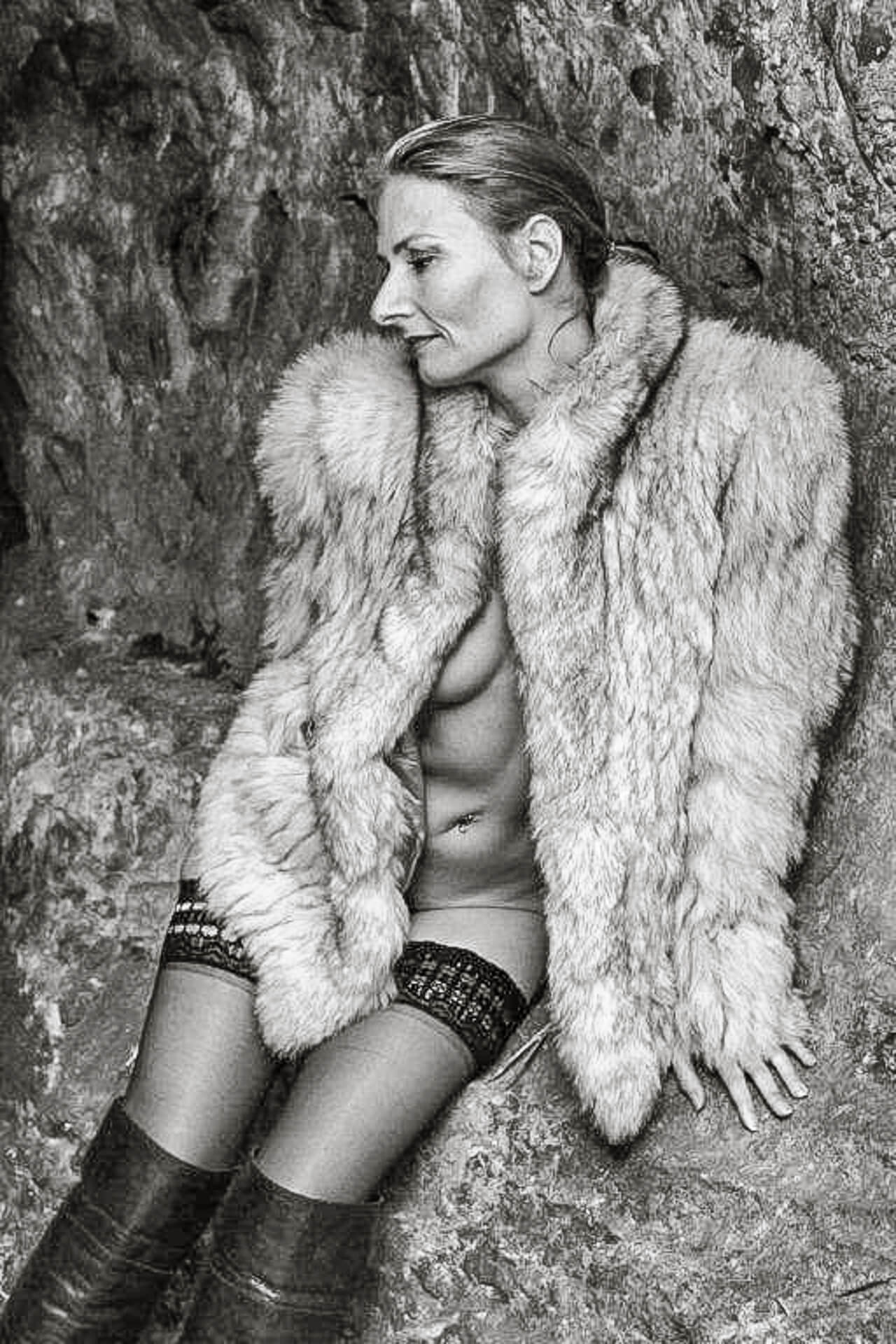 Seen in a 3/4 length black & white image is Liz. Set against a natural rock background, Liz sits on a small ledge. She wears a fake fur coat, closed at the neck but open at the waist, black stockings, and a pair of knee high black leather boots. Liz's body is facing the camera. with her head is turned to her right shoulder, as she looks slightly down. Her left hand is placed flat on the ledge.