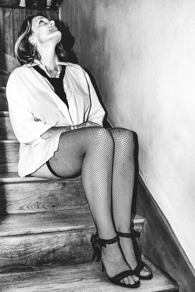 A full length body black & white shot of Pip as she sits on one of the steps of a domestic wooden staircase. There is a wall directly to her LHS. She has her arms crossed on her lap, her head back, and she looks upwards. She wears a white shirt, open to the navel, a black neck tie, black fishnet stockings, and black high heel shoes.