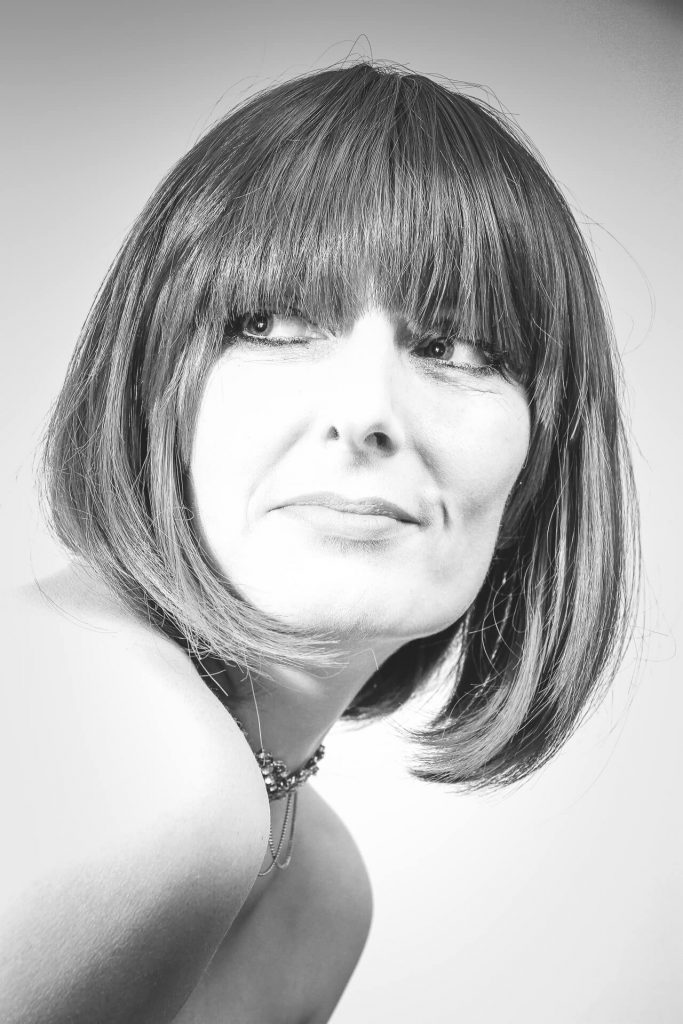 A black & white head & shoulders image of Liz, she wears a 'bob cut' style wig. Liz has her body facing to the right of the image, whilst her head is turned towards the camera as she looks to the left of the image, and slightly above the horizontal. She has a slight grin on her face, and bright smiling eyes.