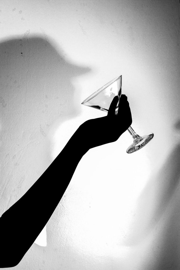 A black & white image which shows Liz's outstretched gloved hand & forearm holding an empty Martini glass, in a drinking pose. On the wall behind this there is a shadow of Liz's hat adorned head and her chest. With it's positioning it makes it appear that the shadow is drinking from the glass in her hand.