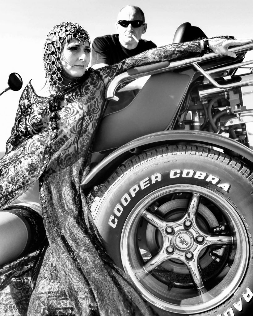 A 3/4 length body shot in black & white of Liz as she sits on the side of a Trike motorcycle. Her body is facing the camera, although she has her head turned away from the camera, and is looking to the right of the image; her outstretched arm rests on one of the bars towards the rear of the trike. Liz wears a chain linked hair piece, an alternative lightweight summer dress which is open to her navel, allowing you to see her black stocking tops. Stood behind her on the far side of the trike is Graham; he is bald. he wears a black t-shirt, and has a cigarette drooping from his mouth, he has adopted a sneering 50's rocker look.