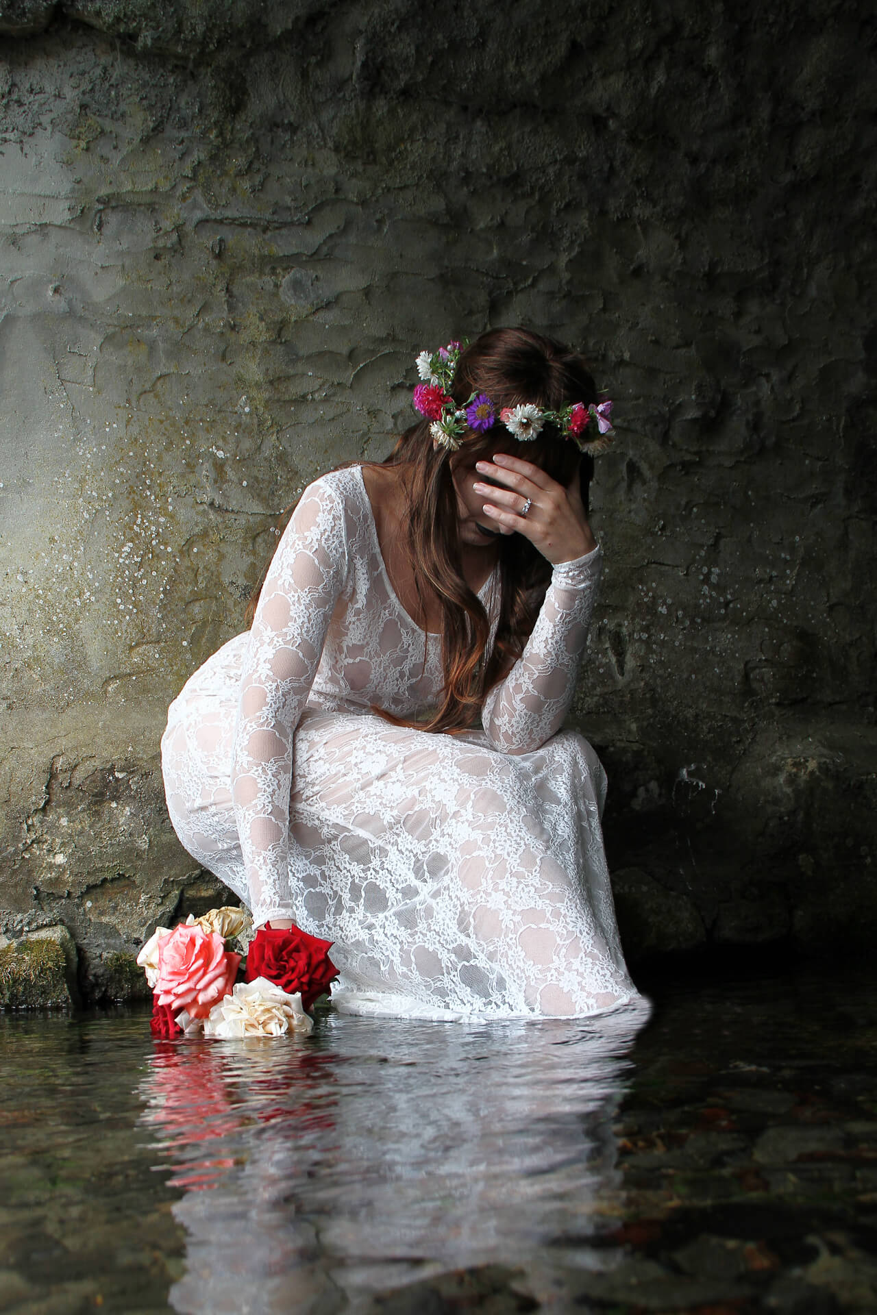 A full length colour image of Liz, in a white lacy wedding dress. She sits under a small bridge on the stone clad edge of the stream, which is flowing under a bridge. She has her feet in the stream, and her dress drags in the current. She has her head down and her left hand is up and covering her eyes, in a dejected pose. She wears a wedding ring, on her left hand, and she also has a garland of multi coloured flowers in her hair. The top half of her body is leaning forwards allowing her long brown hair to fall freely down and over her chest.