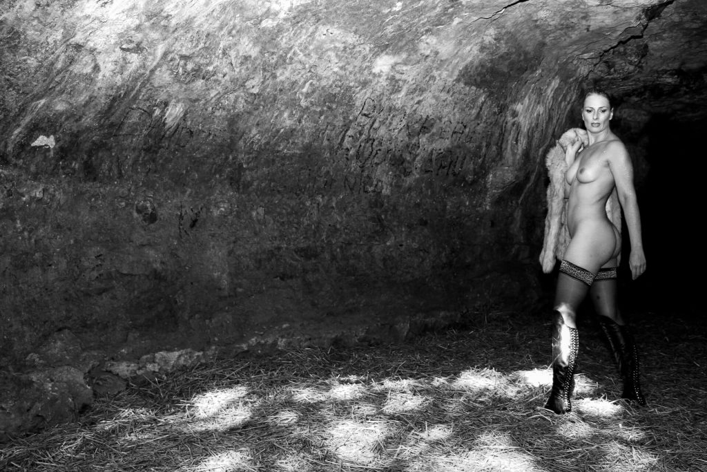 A full length black & white image of Liz taken in a cave entrance in France. She stands feet apart facing away from the camera, but with her top half turned to her left and almost 1/4 on to the camera. She wears only black lace up knee high boots and black stockings, apart from the fake fur coat slung over her right shoulder she is otherwise naked. The pose highlights her extremely well proportioned chest, and a fabulous left bum cheek! She has her head turned towards the camera, but she is looking down just in front of the camera position.