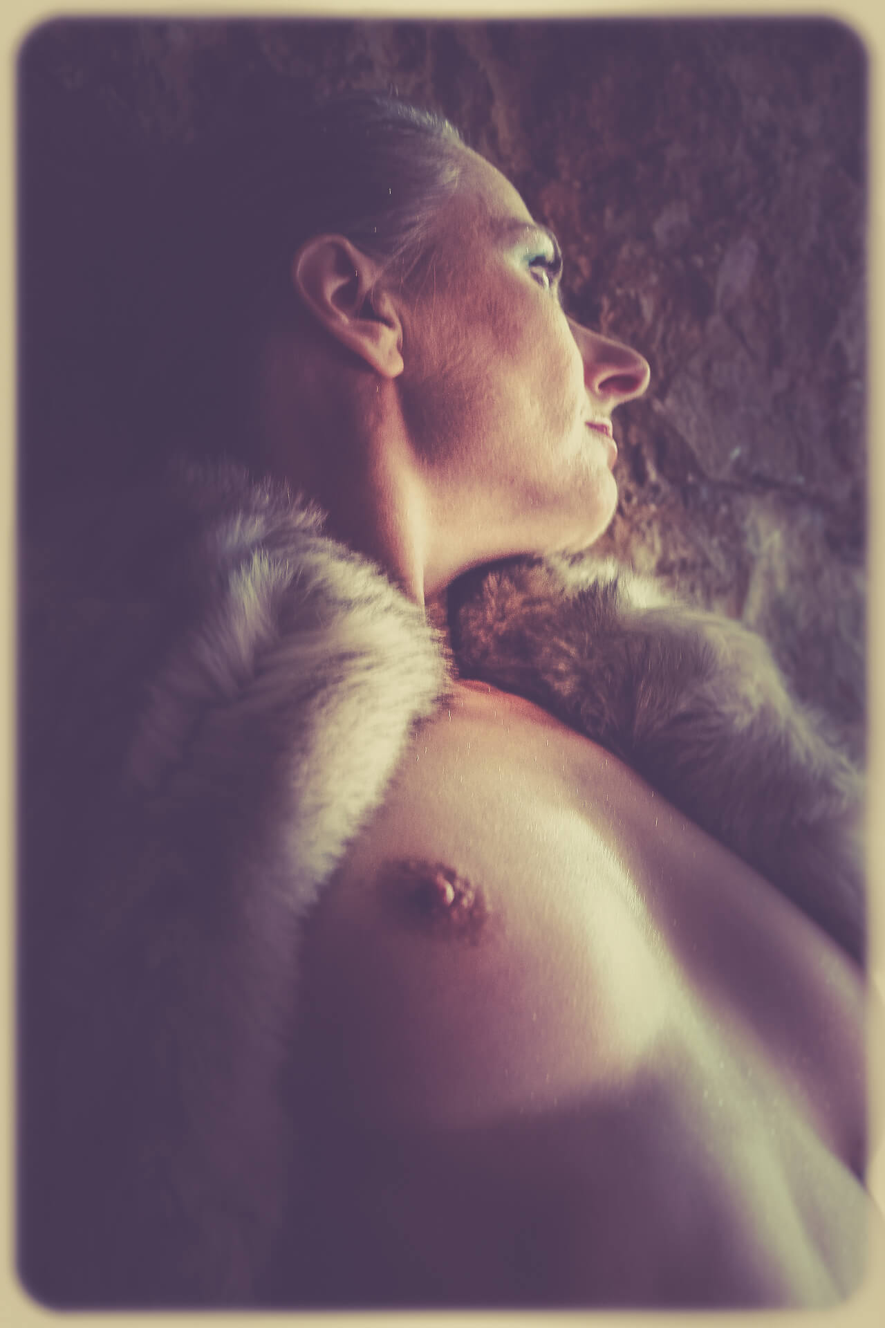 Taken from the right of the subject and from a low angle this waist up colour image of a bare breasted Liz shows her looking out of the cave entrance, off to her left. She wears a fake fur coat over her shoulders, but it is open at the chest allowing her breasts to show. Liz has her hair pulled tightly back, and she leans against the cave wall.