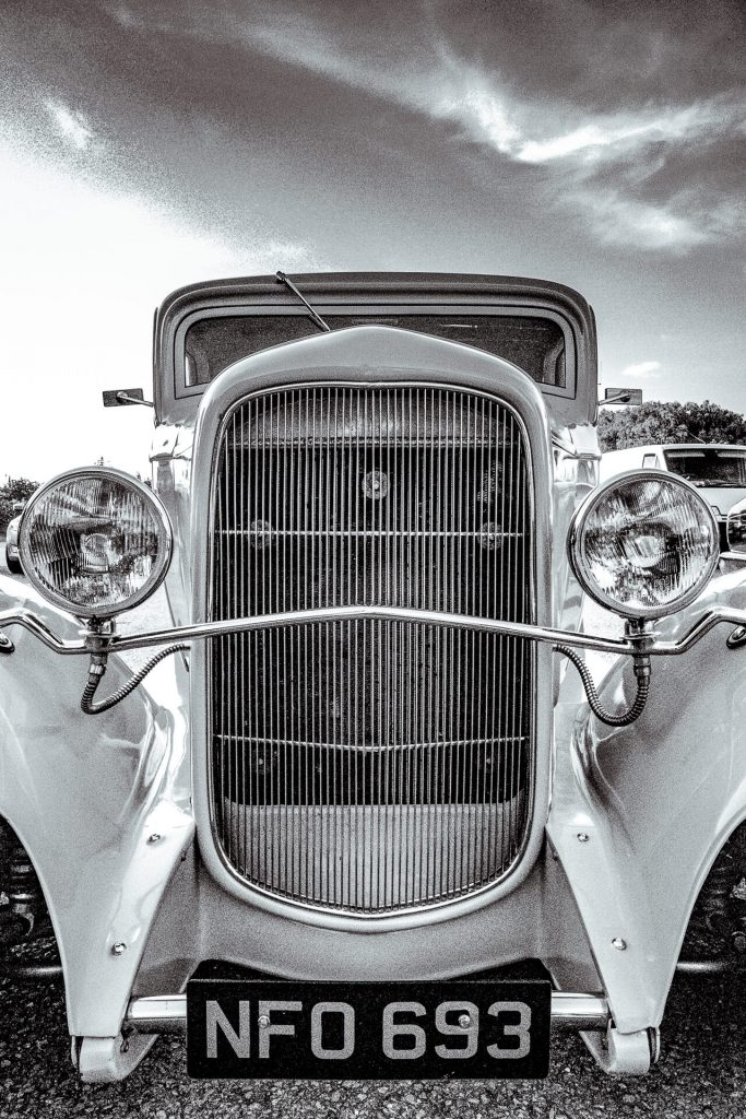Taken from low level a close in black & white image of the front end of a customised car. It has a large radiator grill and two large spotlights mounted on a chrome bar.