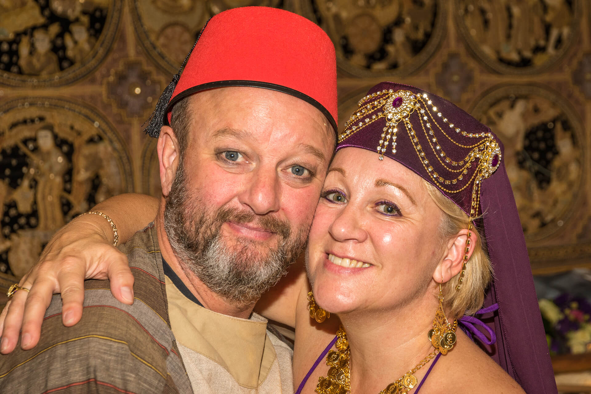 A colour image of a grinning Jane & her brother Dave. Seen in this head & shoulders shot they cozy up for the camera at Jane's Birthday Party. There was a Carry On film fancy dress theme to the evening, Dave wears a 'Carry On Up The Khyber' type robe and Fez, whilst Jane wears the costume of a bellydancer, also from the same film.