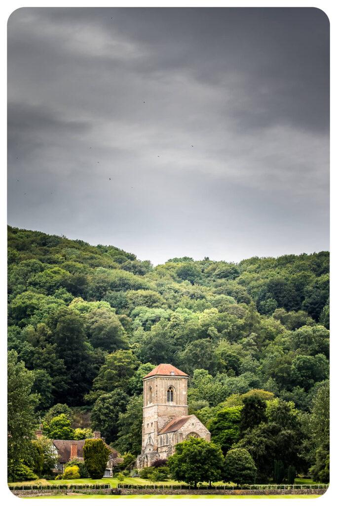 Little Malvern Priory nestles in the wooden hills near Malvern, on an overcast day in 2020