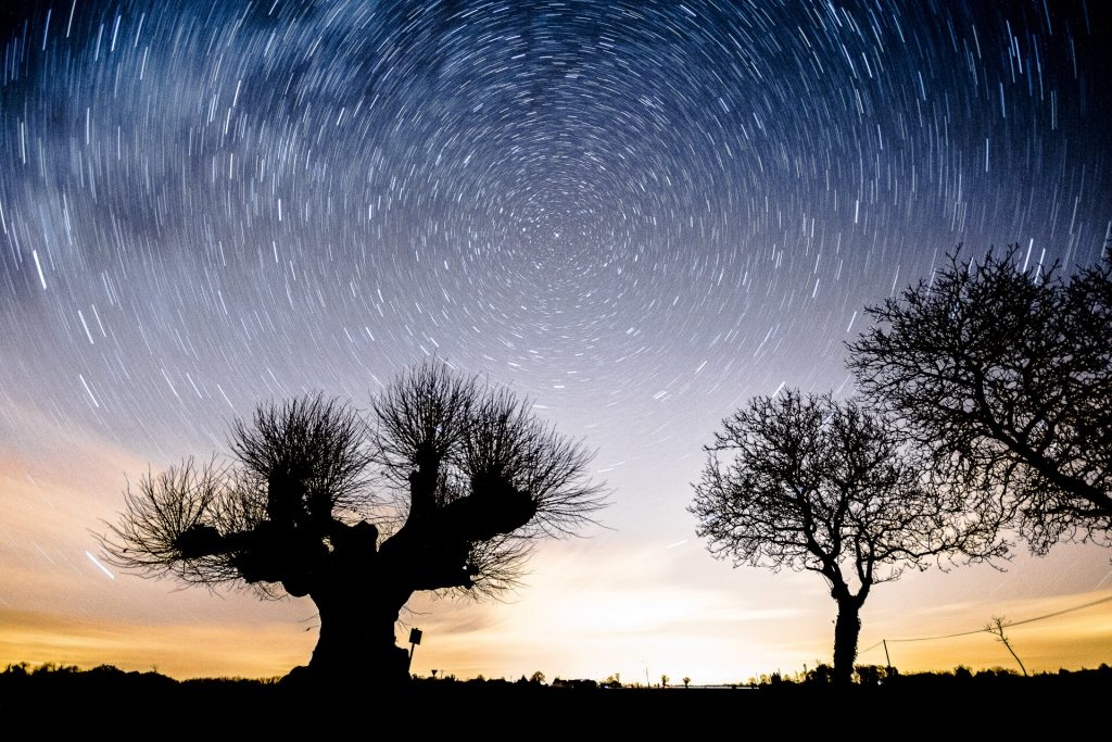 A long exposure photograph showing stars revolving around the North Star. Taken in France in 2017