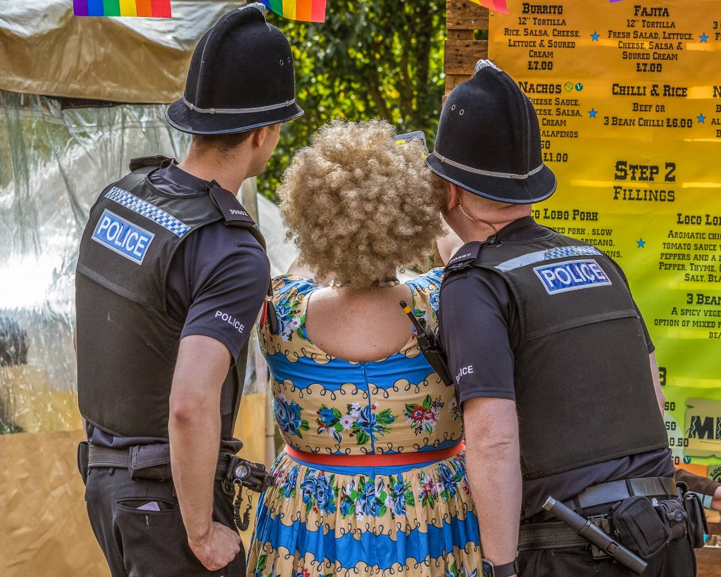 A 3/4 length image, in colour, of a 'female' performer at Worcester Pride 2017. She poses alongside of PC's 30387 & 39862 as 'she' takes a selfie of them all together. They have their backs to the camera as they look into the mobile phone camera.