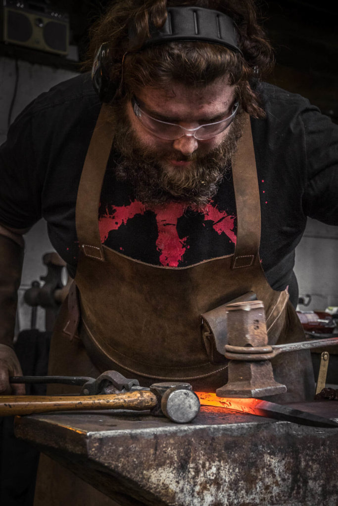 A close up image of blacksmith working red hot metal at a traditional anvil. He wears a leather apron, protective glasses, ear protection, and he has a full beard.