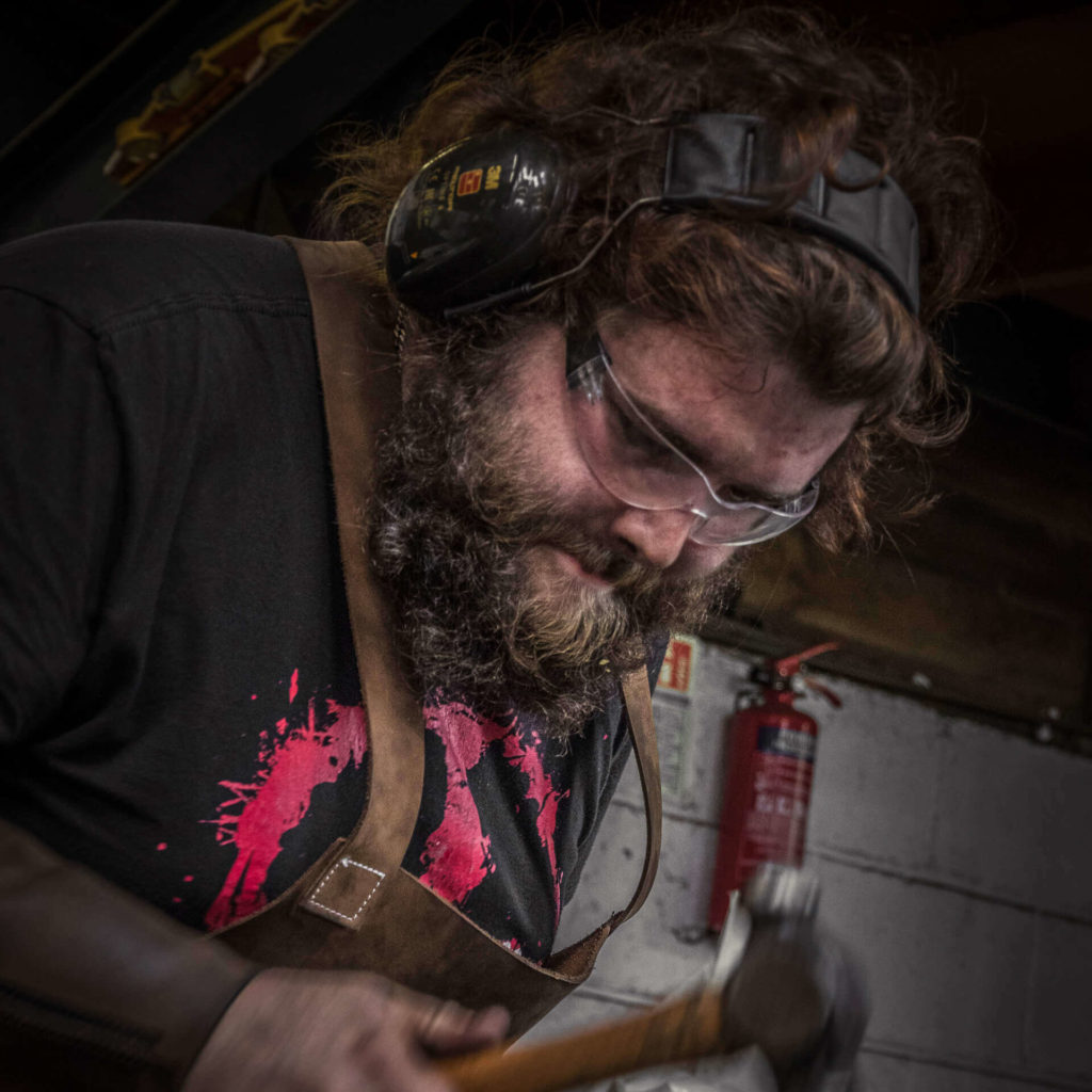 A close up colour image of fully bearded blacksmith working in a smithy with a traditional blacksmiths hammer. He wears a leather apron, protective glasses, and ear protection.