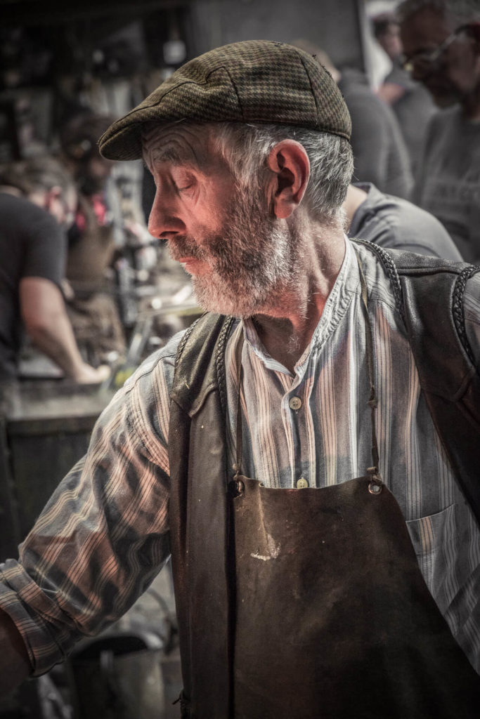 A close up (chest & head) side on colour image of an old & bold blacksmith, who is seen here working in a smithy. He is bearded, and he wears a leather waistcoat and a traditional leather apron over a striped 'Granddad' style shirt, and has a flat cap upon his head. The glow of the forge illuminates his face.
