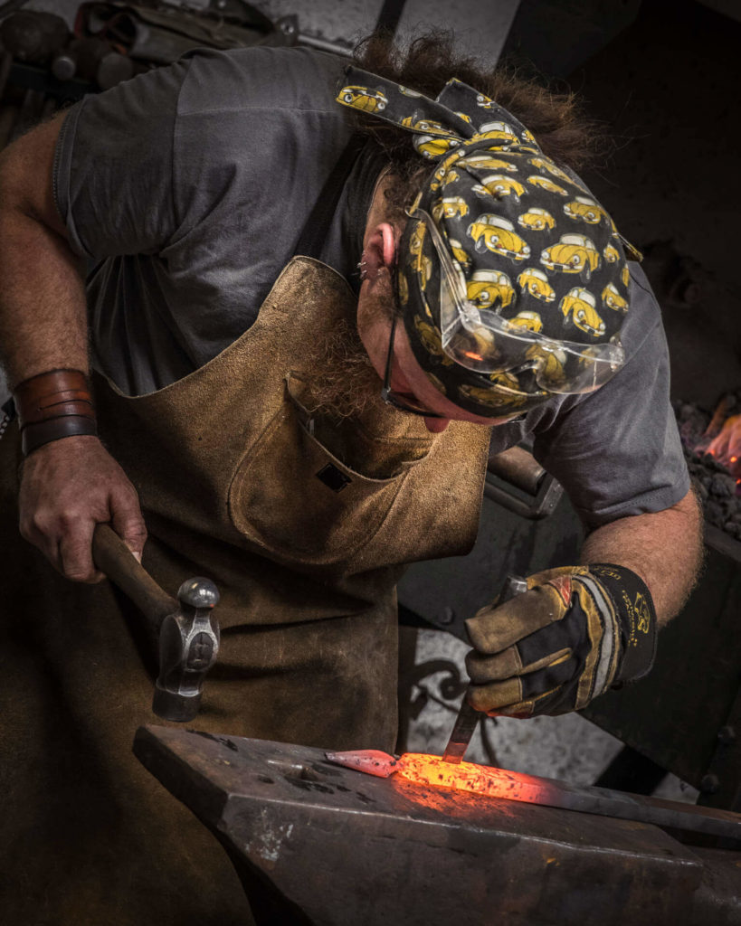 A close up colour image of a blacksmith working a piece of red hot metal on a traditional anvil with a traditional blacksmiths ball-peen hammer. He wears a leather apron, a bandana with cartoon VW Beetles on it, a leather wrist band, a gauntlet on his left hand, and has his protective glasses on the top of his head!