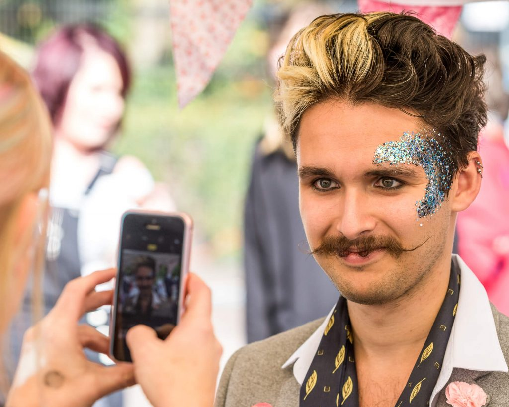 A head & shoulders colour image of a visitor to the Worcester Pride Festival as he waits smiling, for his photograph to be taken by someone on a mobile phone. He has his hair in what is partially bleached quiff, the majority of it is dark coloured, but it also has blonde highlights mixed in there.  Above his left eye and up onto his forehead there is a large crescent shape which appears to be made out of blue glitter; he also sports the beginnings of what could be a 'handlebar moustache'.