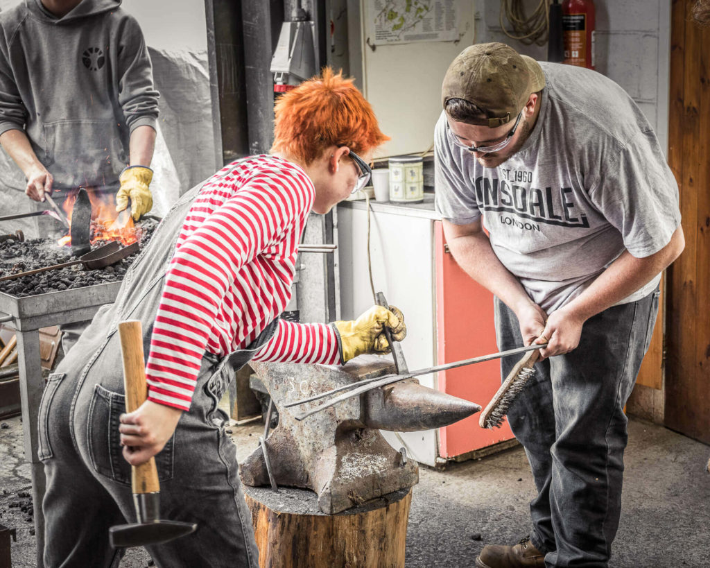A colour image of female blacksmith who is seen splitting a flat metal bar on a traditional anvil with a traditional style blacksmiths hammer and a cold chisel. She is assisted by a male colleague who steadies the metal, he holds a wire brush ready to clean the flat bar. Behind another colleague heats metal in the forge. She wears dungarees, a gauntlet on her left hand, & protective glasses. She has very short ginger spiky hair.