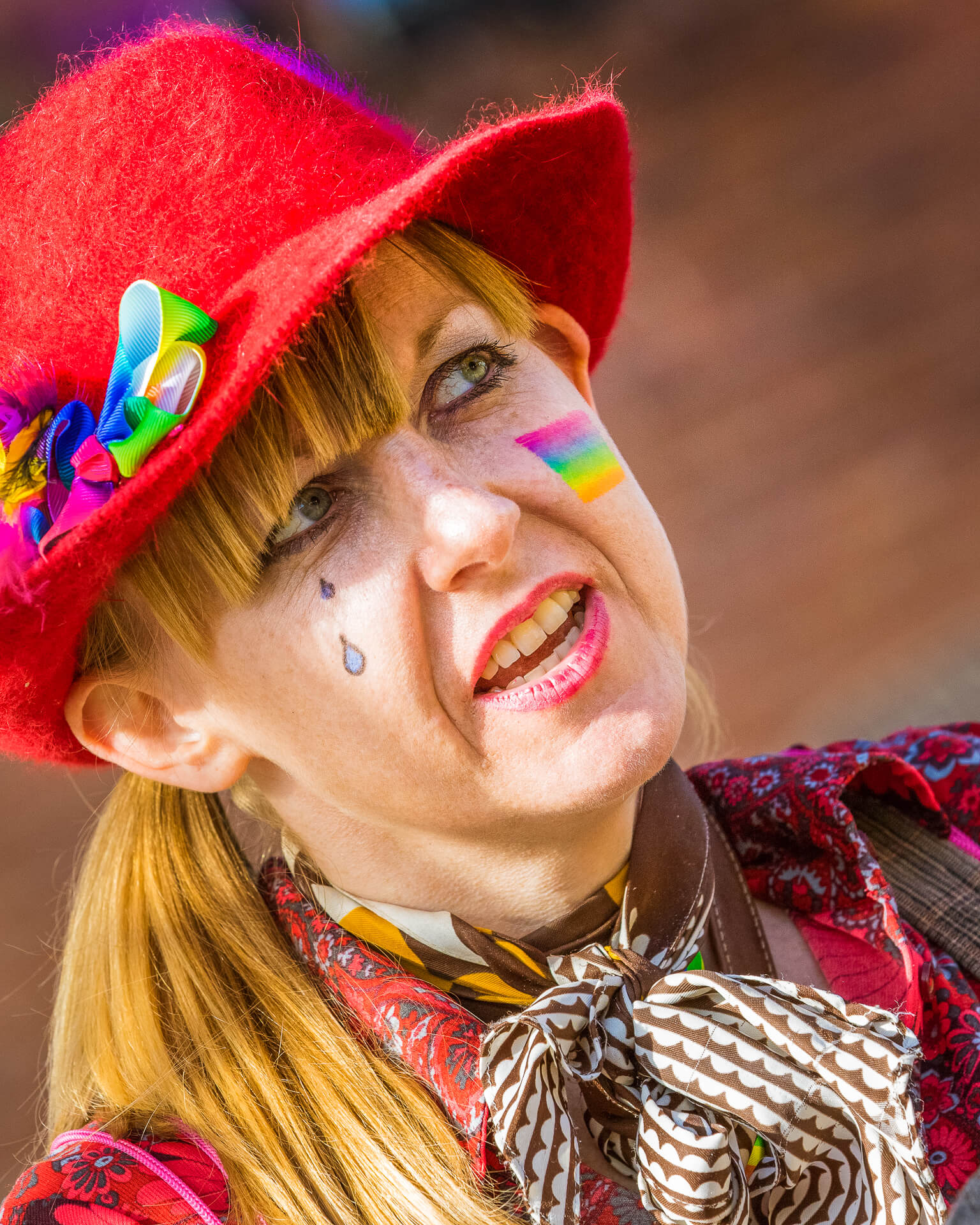 A close up head shot, in colour, of a mime artist whilst she performs at Worcester Pride in 2018. She wears a red floppy felt style hat adorned with a multi coloured bow on the right hand side, which hides her reddish/blonde hair. She has two drawn on teardrops on her right cheek and a 'Rainbow' motif on her left.