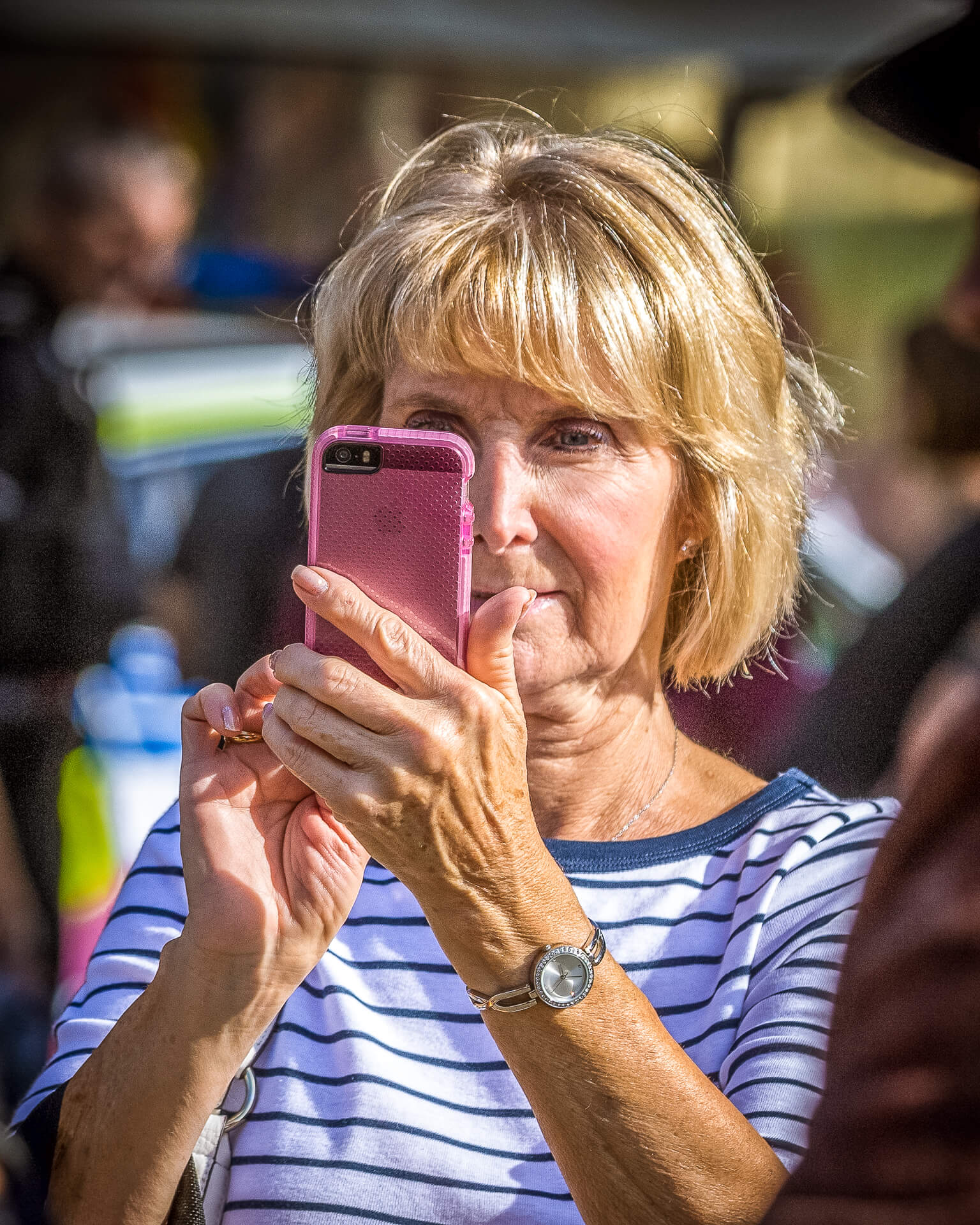 A colour head and chest image of a middle aged lady at Worcester Pride taking a selfie of herself with her pink coloured mobile phone. She has short blonde hair and she wears a white top with blue stripes, she has a look of concentration on her face.