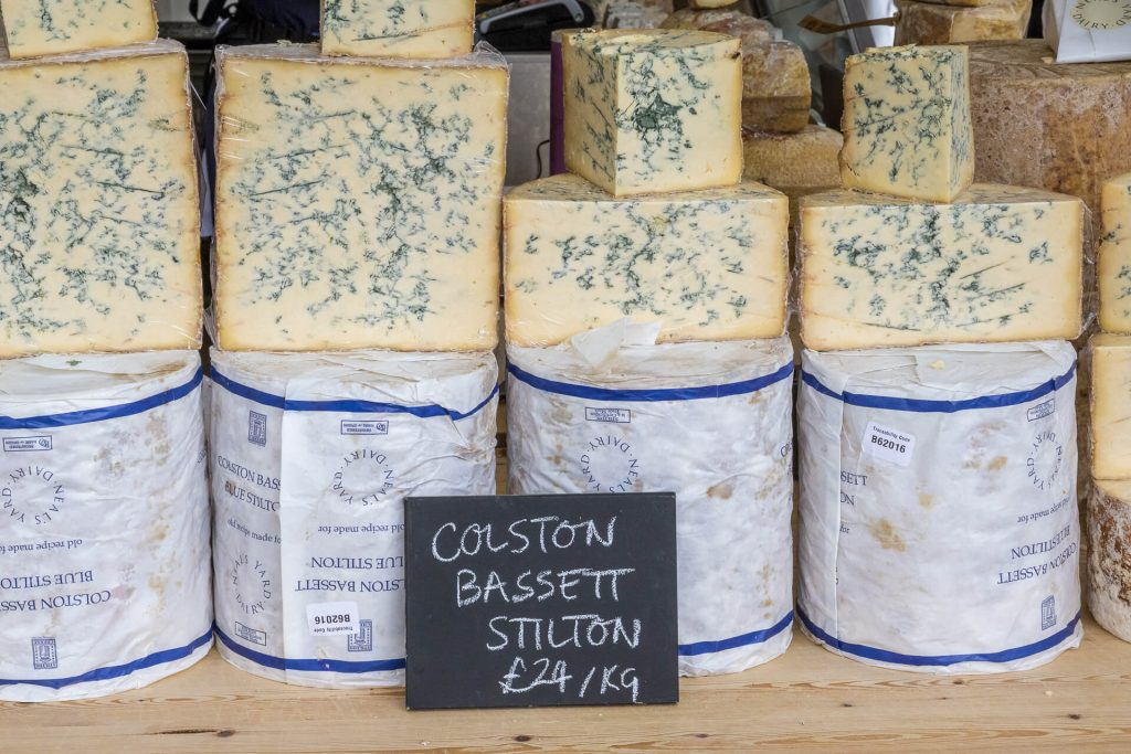 A close up colour view of a selection of Neals Yard Dairy Colston Bassett Stilton Cheese on sale at the 3 Counties Show in Malvern. Some are still wrapped, some are unwrapped and cut into smaller portions. In 2021 it retails at approximately £27 per kilo!